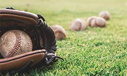 Baseball glove with balls in the grass